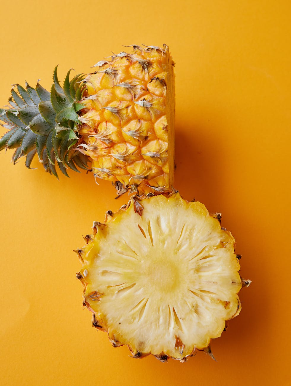 halved tasty tropical pineapple on yellow background
